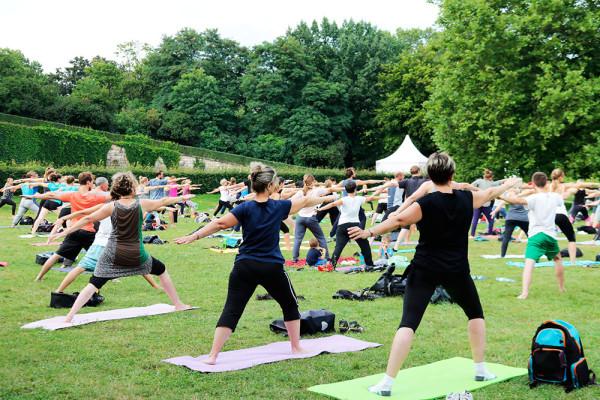 Alle lauschen gespannt den beruhigenden Worten der Lehrerin beim Yoga im Park.