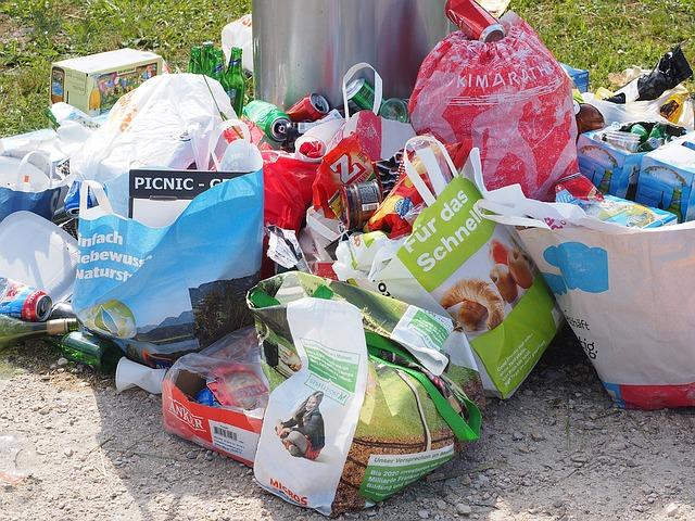 Meterbreit gesammelter Müll neben einer Tonne.